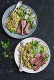 烤牛排和奎奴亚藜菜用结页草在黑暗的背景,顶视图 免版税库存图片