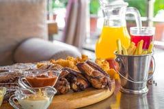 烤牛排和被分类的可口烤肉用炸薯条和冷饮在夏天的桌上 库存照片