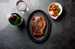 烤牛排在木桌上服务用蕃茄沙拉和红葡萄酒 烤肉, bbq肉牛里脊肉 顶视图 免版税图库摄影