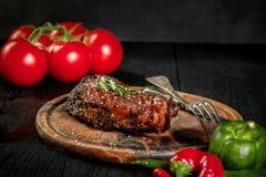 烤牛排晒干用香料和新鲜的草本在一个木板服务用新鲜的蕃茄和红色和青椒 免版税库存图片