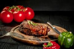 烤牛排晒干用香料和新鲜的草本在一个木板服务用新鲜的蕃茄和红色和青椒 库存照片