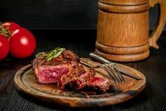 烤牛排晒干用香料和新鲜的草本在有木杯子的一个木板服务啤酒和新鲜的蕃茄 免版税库存照片