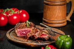 烤牛排晒干用香料和新鲜的草本在有木杯子的一个木板服务啤酒,新鲜的蕃茄,红色 库存图片