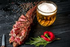 烤牛排晒干用香料和新鲜的草本服务与杯子啤酒,新鲜的红辣椒 免版税库存图片