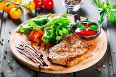 烤牛排猪肉用新鲜蔬菜沙拉、蕃茄和调味汁在木切板 库存照片