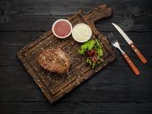 烤牛排用在委员会的调味汁 黑暗的木桌 图库摄影