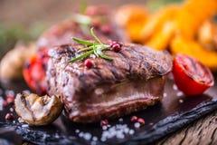 烤牛排用迷迭香、盐和胡椒在老切板 贝多芬 库存图片