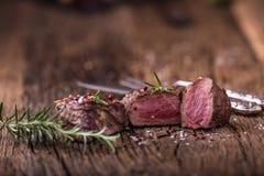 烤牛排用迷迭香、盐和胡椒在老切板 贝多芬 图库摄影