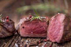 烤牛排用迷迭香、盐和胡椒在老切板 贝多芬 免版税库存图片