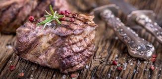 烤牛排用迷迭香、盐和胡椒在老切板 贝多芬 免版税图库摄影