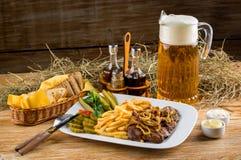烤牛肉、炸薯条和水罐啤酒 免版税图库摄影