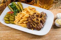 烤牛肉、炸薯条和水罐啤酒 库存照片