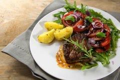 烤牛肉小腓厉牛排用土豆和蕃茄芝麻菜沙拉 免版税库存图片