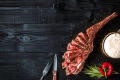 烤牛肉干燥年迈的肋骨用香料、菜和一杯在黑木背景的低度黄啤酒特写镜头 库存图片