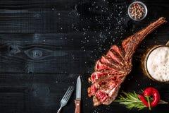 烤牛肉干燥年迈的肋骨用香料、菜和一杯在黑木背景的低度黄啤酒特写镜头 免版税库存照片