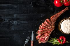 烤牛肉干燥年迈的肋骨用香料、菜和一杯在黑木背景的低度黄啤酒特写镜头 库存照片