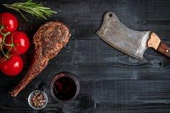 烤牛肉干燥年迈的肋骨用香料、菜和杯在黑木背景的红葡萄酒特写镜头 免版税库存照片