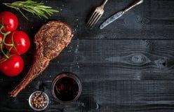 烤牛肉干燥年迈的肋骨用香料、菜和杯在黑木背景的红葡萄酒特写镜头 库存图片