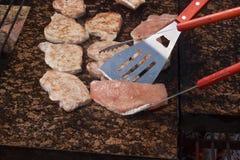 烤猪排和鸡在一个热的花岗岩工作台面 与烤肉的夏天党 烤在一块热的石头 免版税图库摄影