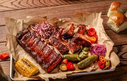 烤猪排服务用烤玉米、salat、bbq调味汁、盐胡椒和黄瓜在羊皮纸在木 库存照片