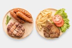 烤猪排牛排,香肠用在w隔绝的炸薯条 库存图片