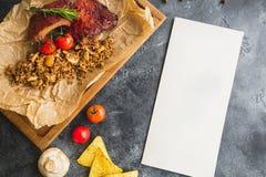 烤猪排用荞麦、蘑菇和蕃茄在老木切板 平的位置,顶视图 与拷贝spac的纸牌 免版税库存照片
