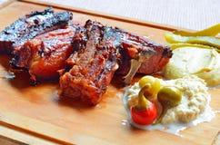 烤猪排用辣椒和开胃菜在木 库存图片