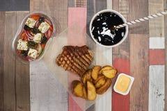 烤猪肉、土豆、沙拉和柠檬水 库存照片