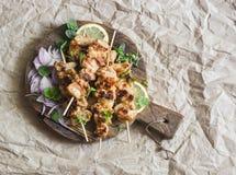 烤猪肉串用烂醉如泥的红洋葱和薄菏在一个土气切板在纸背景 可口夏天午餐 库存照片