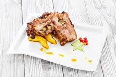 烤猪肉充塞用蘑菇、桃子、阳桃、蔓越桔和甜调味汁在板材在木背景 免版税库存照片