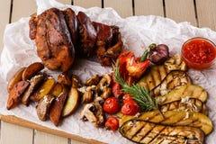 烤猪肉指关节用烤蕃茄、蘑菇、vagetable骨髓、茄子、红色甜椒和被烘烤的土豆 库存照片