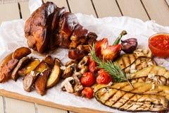 烤猪肉指关节用烤蕃茄、蘑菇、vagetable骨髓、茄子、红色甜椒和被烘烤的土豆 免版税库存图片