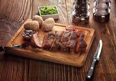 烤猪肉牛排裁减成在一个木立场的切片 免版税库存图片