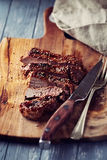 烤猪肉用在木砧板的黑胡椒,被切 图库摄影