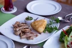 烤猪肉用烤黏米饭和辣调味汁在一个餐桌集合上把用菜装饰的盘放 库存照片