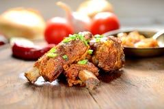 烤猪肉肋骨、蕃茄和其他菜在木背景 库存图片