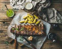 烤猪肉肋骨用调味汁、油煎的土豆和黑啤酒 图库摄影