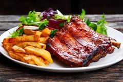 烤猪肉肋骨,在白色板材的油煎的土豆有菜的 库存照片