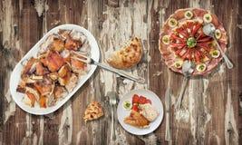 烤猪肉肩膀切片用开胃菜装饰了美味盘并且发酵了在老土气被风化的破裂的fl供食的小面包干 库存图片