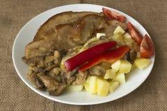 烤猪肉腹部有土豆和蘑菇视图 免版税库存照片