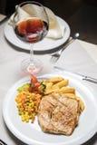 烤猪腰、配菜和酒 免版税库存照片