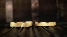 烤的两片面包片特写镜头  r 在格栅的烤箱油煎的芬芳简单的面包切片 在格栅的多士 股票录像