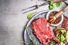 烤的牛排调味料与BBQ或与涂抹刷子的美味调味汁和在灰色石背景,顶视图用卤汁泡 库存照片