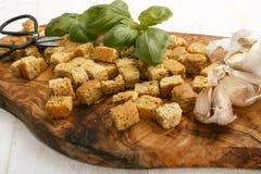 烤箱在一个木板的被烘烤的油煎方型小面包片 库存图片
