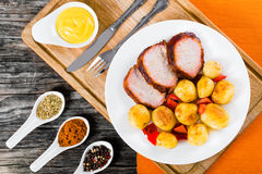 烤箱烘烤了与猪排、芥末和香料的嫩土豆土豆 库存图片