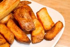 烤箱烘烤了在一块白色板材的土豆片 免版税库存照片