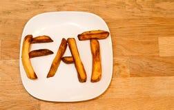 烤箱烘烤了在白色板材拼写的FAT的土豆片 库存照片