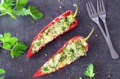 烤箱煮熟的红色辣椒粉充塞用乳酪、大蒜和草本在抽象灰色背景 概念吃健康 免版税库存照片