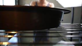 从烤箱的看法:妇女采取烤盘并且关闭烤箱` s门 美丽的女孩在她的厨房采取她的蛋糕 股票视频