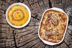 烤箱被烘烤的菜炖煮的食物用鸡肉和碗老树桩被风化的破裂的顶面上的被装饰的俄国沙拉集合 免版税库存图片